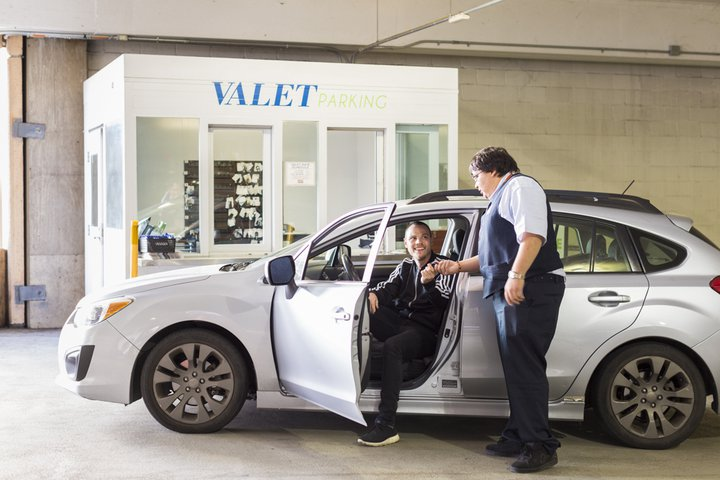 a person in a car talking to a valet